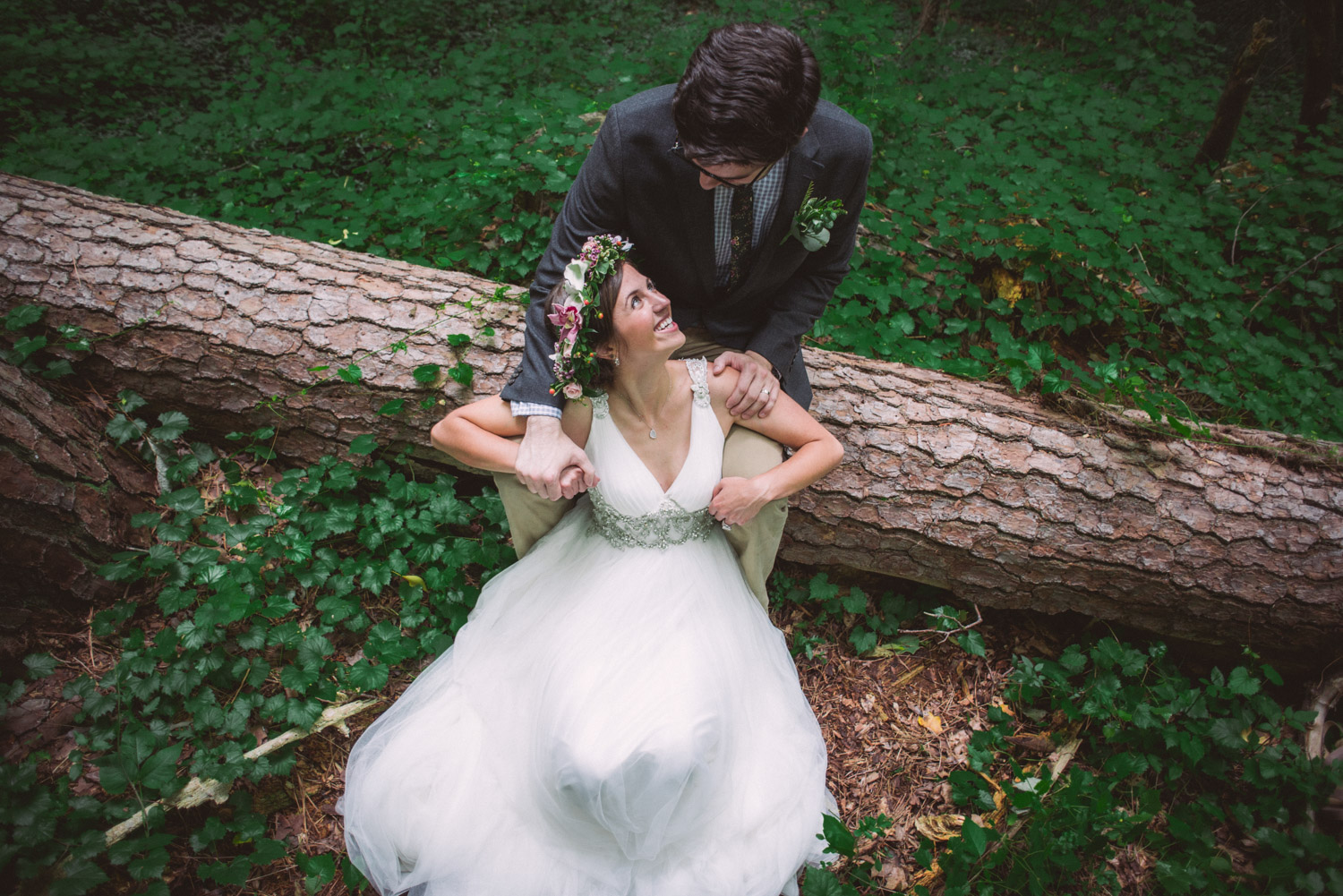 a bride & groom sitting in the woods
