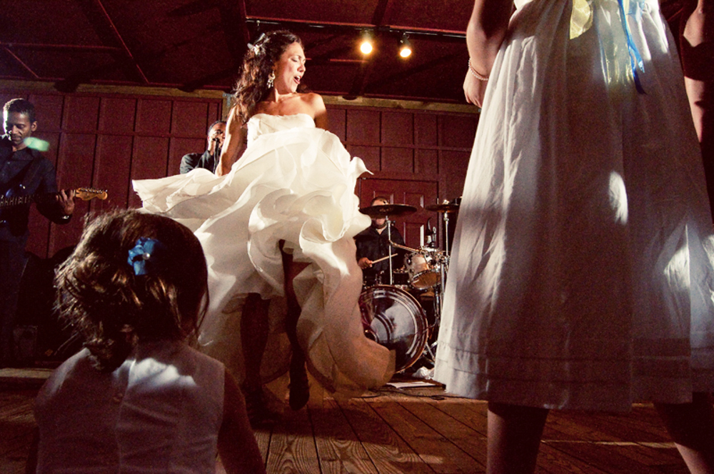 A bride dancing on stage, at her wedding with the best weddings songs to dance to