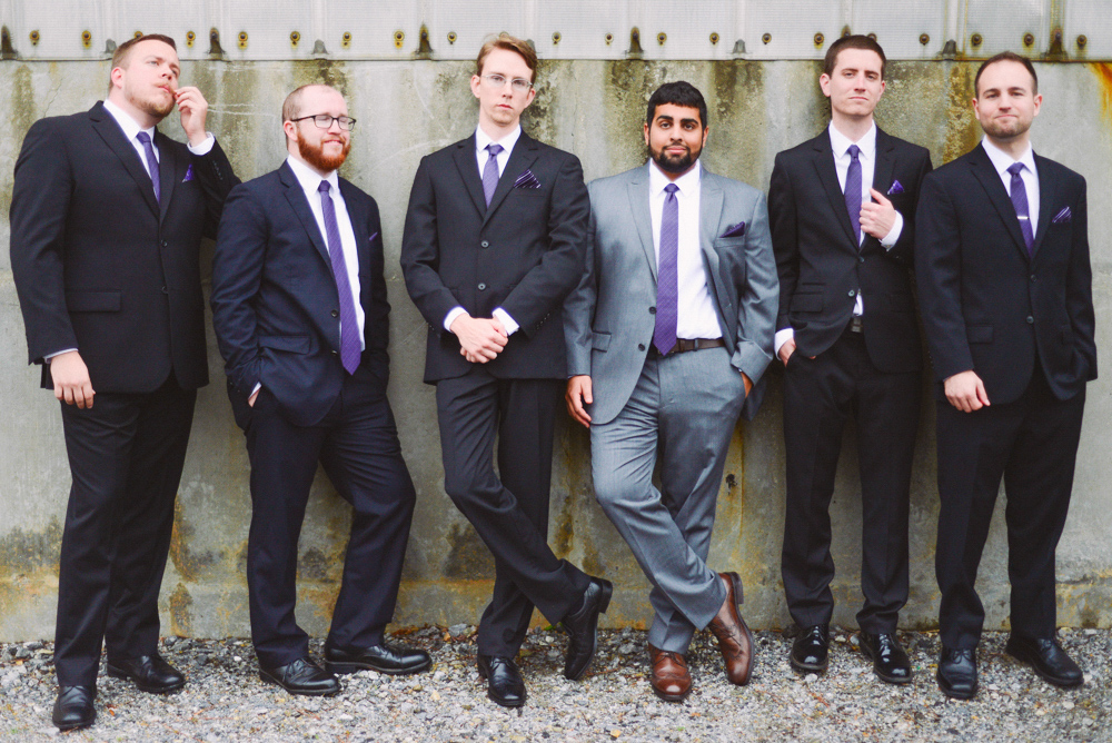 A man and his groomsmen stand outside the Foundry at Puritan Mill