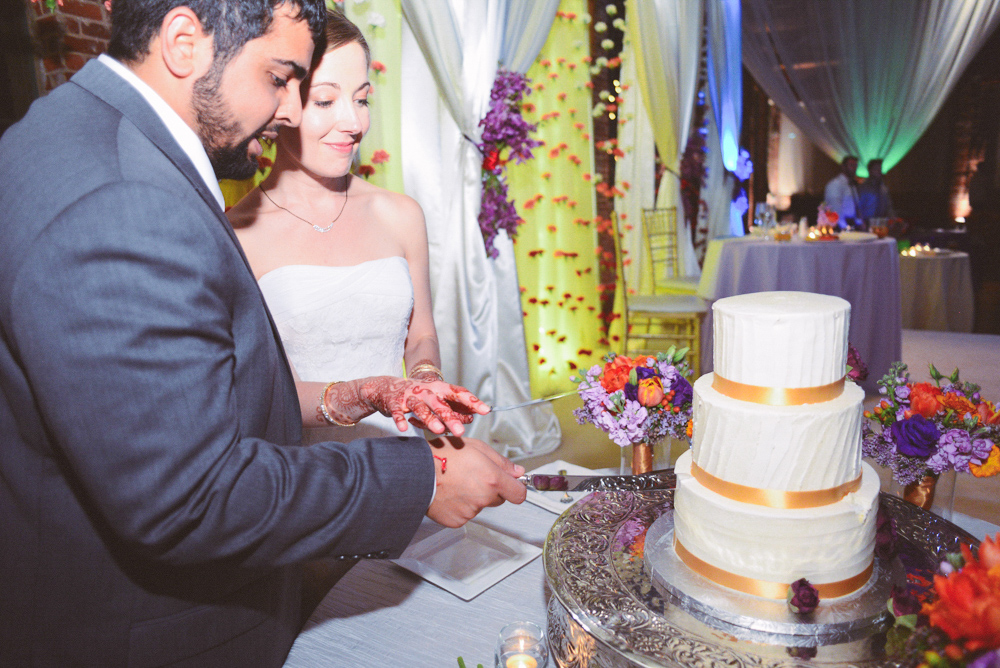 A wedding couple cut their wedding cake at the Foundry at Puritan Mill