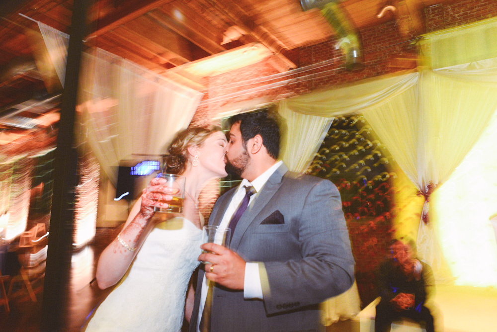 A wedding couple kiss during their wedding reception at the Foundry at Puritan Mill