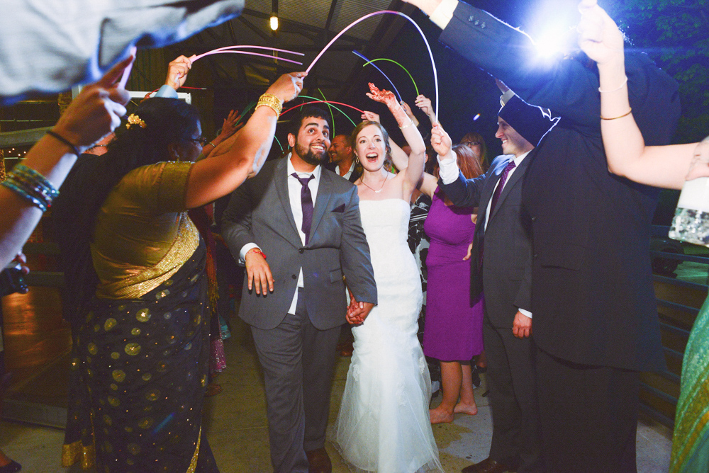 A couple exit their wedding at the Foundry at Puritan Mill